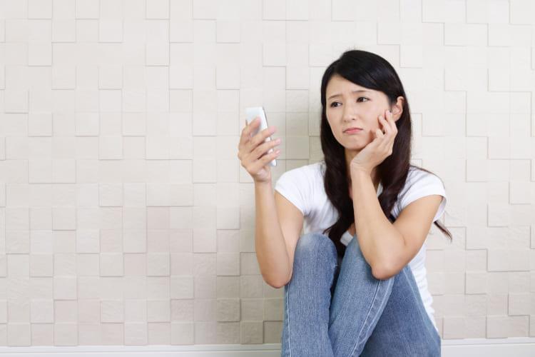 携帯を見てショックを受ける女性