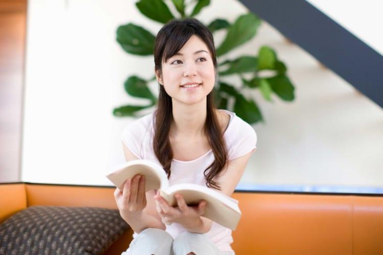 家で本を読む女性