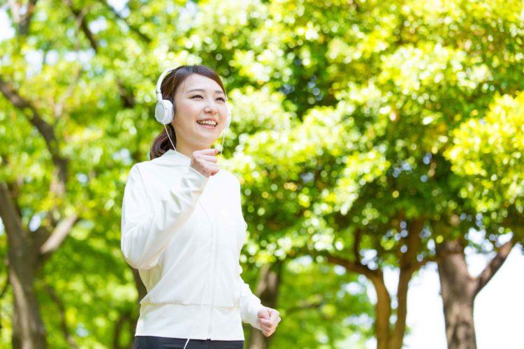 ヘッドホンで音楽を聴きながらジョギングする女性