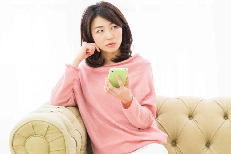フリマアプリを見ながら検討する女性