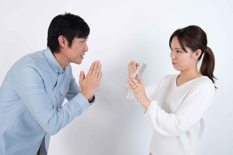 男性にスマホを見せて怒る女性